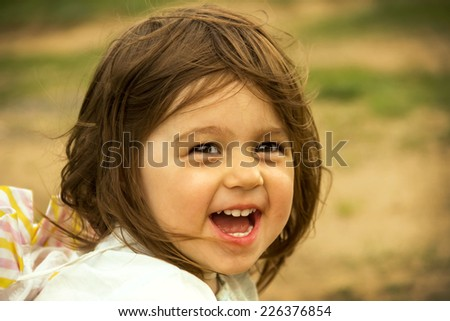 cute kid is playing on send in sunny day - stock photo