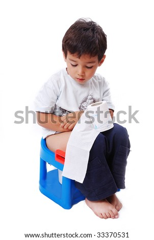 Cute kid is sitting on toilet and holding toilet paper