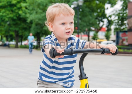 Cute kid learning to ride his first bicycle