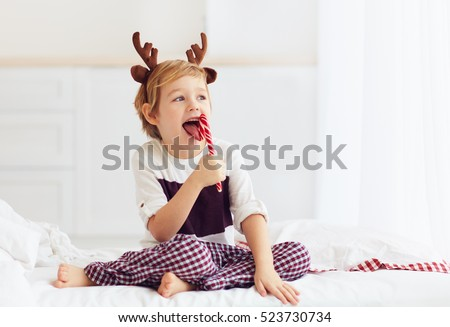 cute kid licking christmas candy in the winter morning