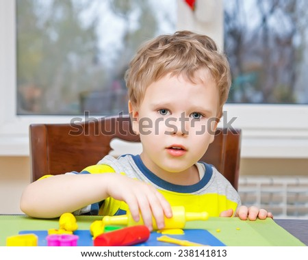 Cute kid modeling with colorful plasticine