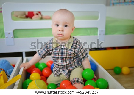 Cute kid or child playing colorful balls looking down