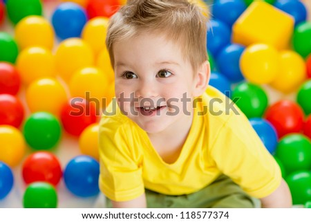 Cute kid or child playing colorful balls top view - stock photo