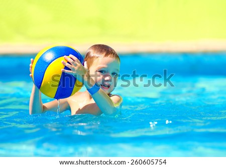 cute kid playing in water sport games in pool - stock photo