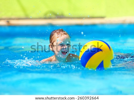 cute kid playing water sport games in pool - stock photo