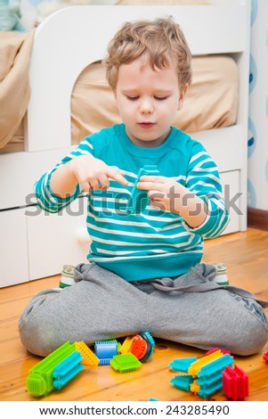 Cute kid playing with colorful bristle blocks