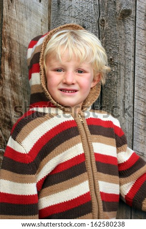 Cute kid with a striped wool sweater. - stock photo