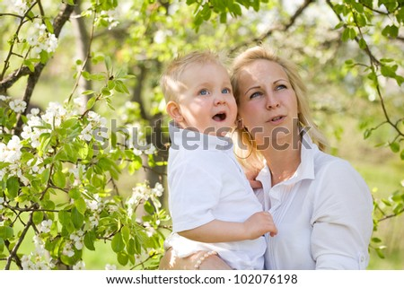Cute kid with his mom outdoors in nature at spring. - stock photo