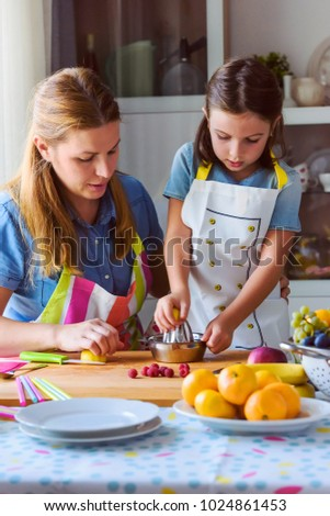 Cute kid with mother preparing a healthy fruit snack in kitchen