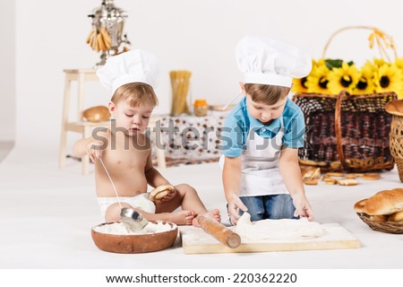 Cute kids, adorable little girl and funny baby boy wearing chef hats playing with dough baking a pie in a sunny white kitchen - stock photo