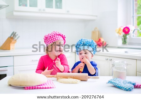 Cute kids, adorable little girl and funny baby boy wearing pink and blue chef hats playing with dough baking a pie in a sunny white kitchen - stock photo