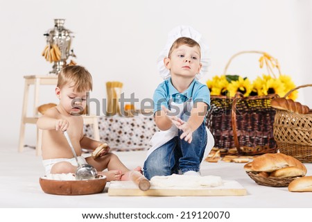 Cute kids, adorable little girl and funny boy wearing chef hats playing with dough baking a pie in a sunny white kitchen - stock photo