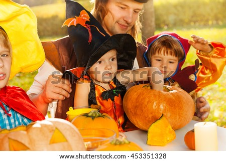 Cute kids and father in Halloween costumes