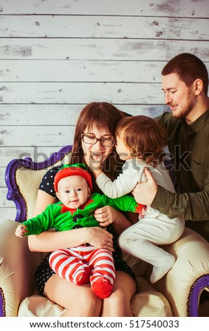 cute kids and their wonderful parents sitting together on white chair