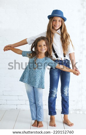 Cute kids 5 and 8 years old wearing trendy blue clothes posing over white brick wall - stock photo