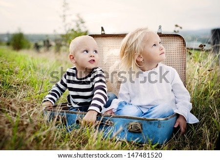 Cute kids are having fun in the old suitcase - stock photo