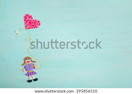 Cute Kids Art of Girl Flying Pink and Red Valentine's Day Heart Kite on Rustic Blue Cyan Painted Wood Board Background with Room or Space for Copy, Text, Your Words.  Above looking down horizontal. - stock photo