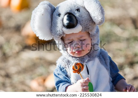 Cute kids in Halloween costumes at the pumpkin patch. - stock photo