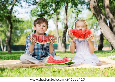 Cute kids in park eating juicy watermelon