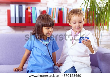 cute kids playing doctors in office - stock photo
