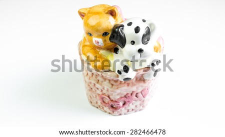 Cute kitten cat and dalmatian puppy dog figure sitting on porcelain jar with letter Cookie on it. Concept of cat or dog pet cookie jar. Isolated on white background. Copy space. - stock photo