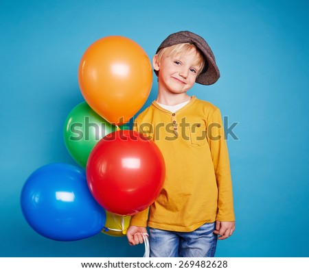 Cute lad with multi-color balloons looking at camera - stock photo