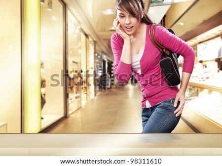 Cute lady looking at a shop window in shopping center - stock photo