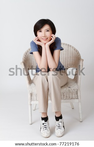 Cute lady of Asian sitting on chair, full length portrait isolated on gray studio background.