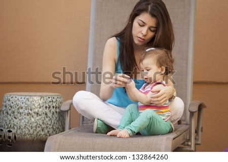 Cute latin mother and her daughter spending some time outdoors - stock photo