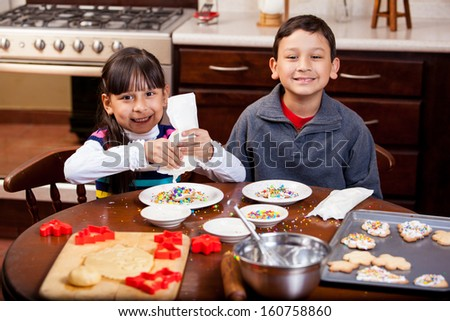 Cute Latin siblings baking and decorating Christmas cookies and smiling