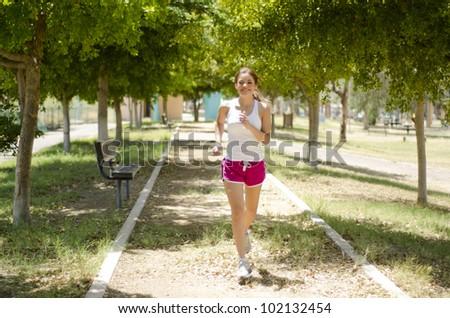 Cute latin woman running at the park - stock photo