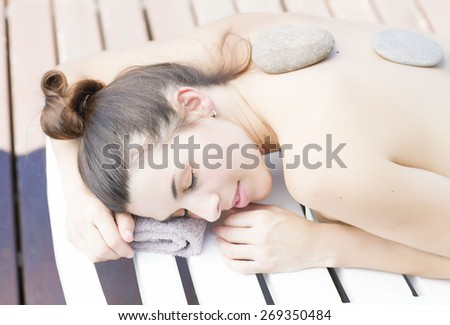 Cute latina girl receiving a massage at the spa - stock photo
