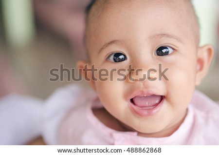 Cute laughing and smiling Asian baby girl at home