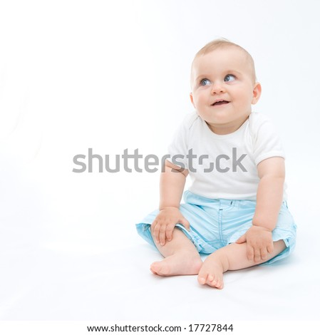 cute laughing baby boy sitting on white background - stock photo