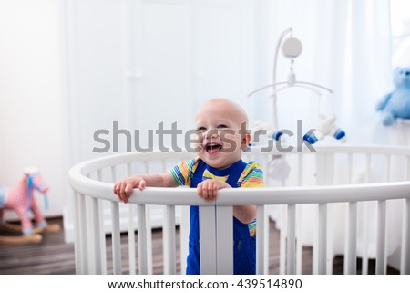 Cute laughing baby standing in a white round bed. White nursery for young children. Little boy learning to stand in his crib. Toys for infant cot. Smiling child playing with toy bear in sunny bedroom. - stock photo