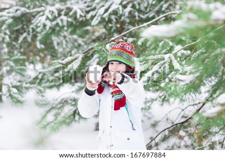Cute laughing boy playing snow ball fight in a snowy forest - stock photo