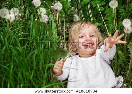 Cute laughing caucasian girl two years old lying on the grass with dandelions, happy child having fun in spring park - stock photo