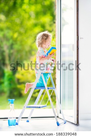 Cute laughing curly toddler girl washing big window with squeegee in white living room with door into garden, standing on ladder with blue bucket with water, detergent solution spray bottle and sponge - stock photo