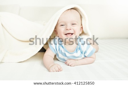 Cute laughing 6 month baby boy lying under the blanket on bed