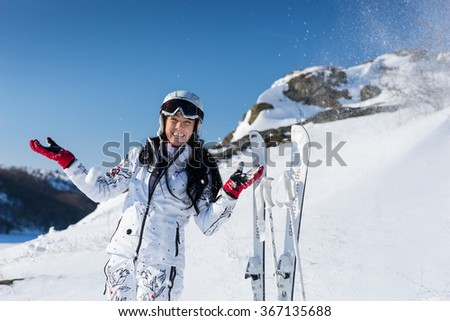 Cute laughing woman in white snowsuit and helmet next to skis stuck in ground being hit with spray of snow