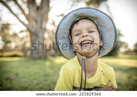 Cute laughing 4 year old mixed race Asian Caucasian boy wearing a hat and playing outside in the summer sun - stock photo