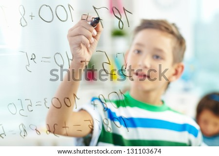 Cute learner doing sums with schoolmate on background - stock photo