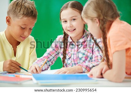 Cute learner looking at camera at lesson of drawing with her classmates near by - stock photo