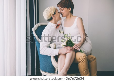 Cute lesbian couple in wedding outfits sitting in the armchair. Gay marriage concept.. Toned picture. Selective focus - stock photo