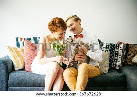 Cute lesbian couple in wedding outfits sitting with their cat. Gay marriage concept. Selective focus - stock photo