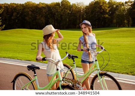 cute lesbians with a hats walking with a bicycle on park - stock photo
