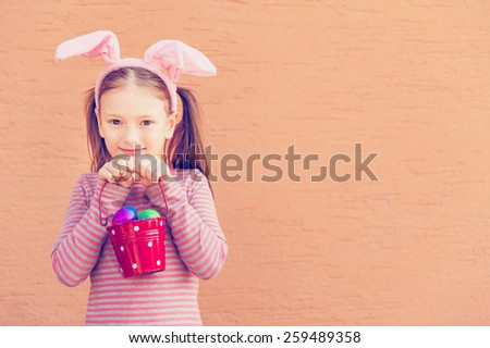 Cute liitle girl wearing rabbit ears, holding bucket with colorful easter eggs, toned image, instagram effect - stock photo