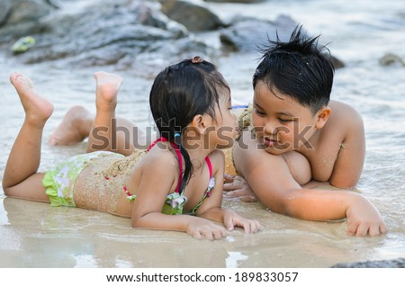 cute litte boy and girl talking on the beach