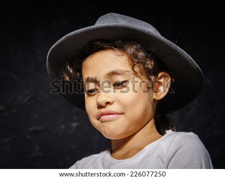 Cute little african-american girl in hat portrait on black - stock photo