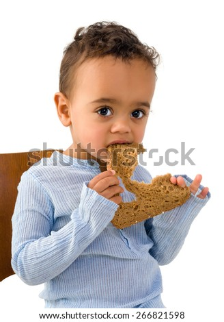 Cute little African boy eating a slice of wholemeal bread - stock photo